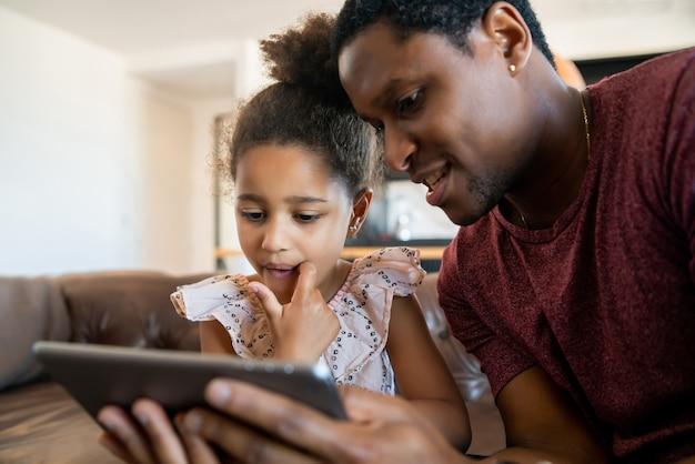 Portret van een dochter en vader met behulp van een digitale tablet tijdens het verblijf thuis