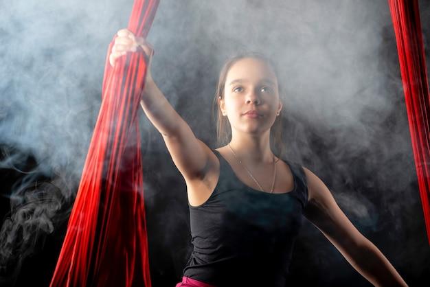 Portret van een doelgericht mooi tienermeisje met rode linten in de lucht