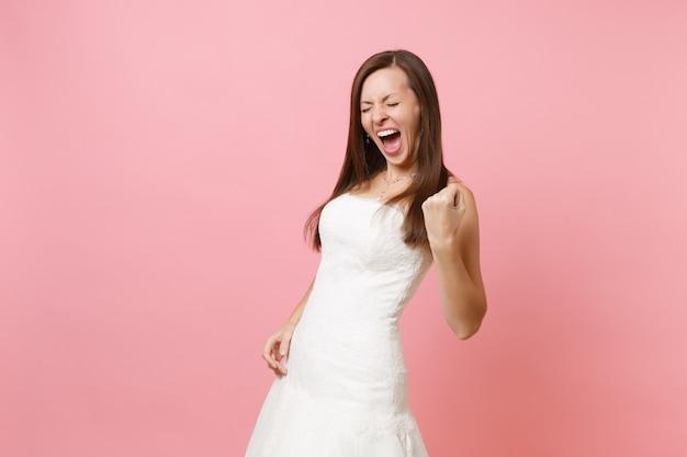Portret van een dolblije vrouw in een witte jurk die een winnaargebaar doet en de vuist balt