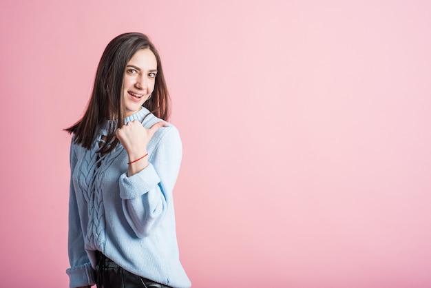 Portret van een donkerbruin meisje op een roze achtergrond die haar duim naar copyspace richt