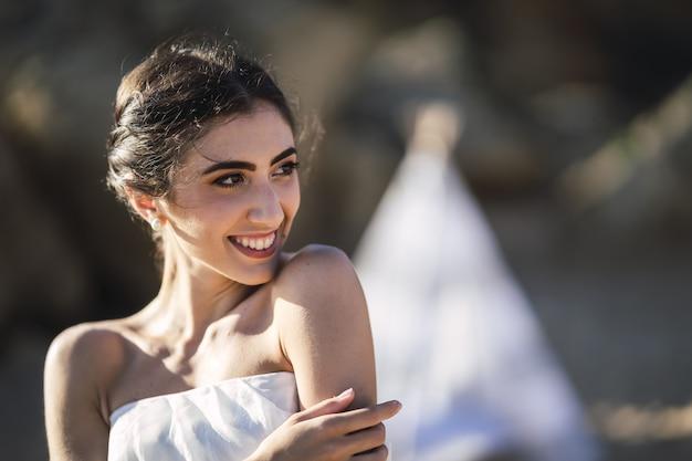 Portret van een donkerbruine kaukasische bruid met een natuurlijke gelukkige glimlach op haar gezicht