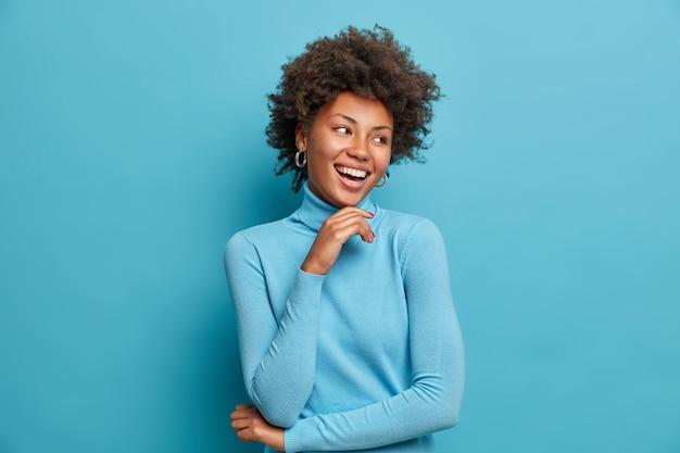 Portret van een donkere vrolijke vrouw met krullend haar, raakt kin zachtjes, lacht gelukkig, geniet van vrije dag, voelt zich gelukkig en enthousiast, hoort iets positiefs, draagt casual blauwe coltrui