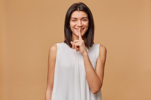 Portret van een donkerharig meisje dat gelukkig lachend stiltegebaar toont, vraagt om geheim te houden met wijsvinger op de lippen, geïsoleerd