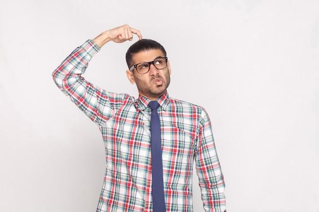 Portret van een doordachte knappe bebaarde zakenman in een kleurrijk geruit overhemd, een blauwe stropdas en een bril die staat en wegkijkt met een grappig gezicht. indoor studio opname, geïsoleerd op een grijze achtergrond.