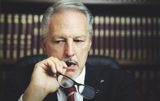 Portret van een doordachte manager in zijn kantoor houdt zijn bril