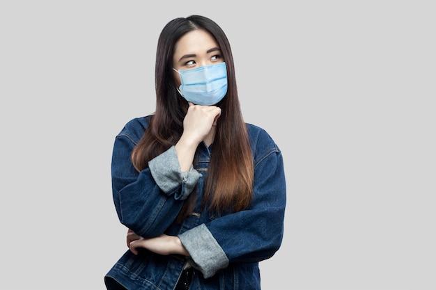 Portret van een doordachte, mooie aziatische jonge vrouw met een chirurgisch medisch masker in een blauw spijkerjasje dat staat, verward wegkijkt en denkt. indoor studio opname, geïsoleerd op lichtgrijze achtergrond.