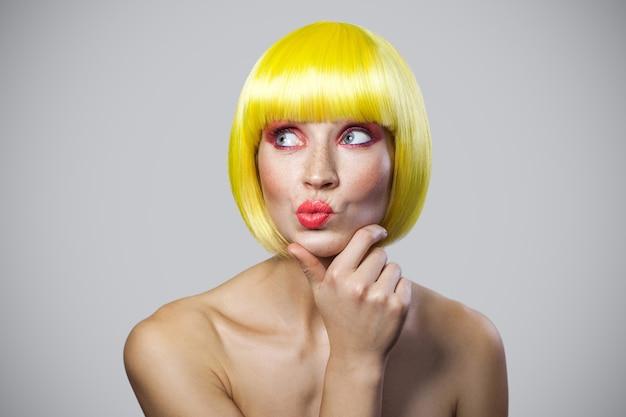 Portret van een doordachte schattige jonge vrouw met sproeten, rode make-up en gele pruik die haar kin aanraakt, wegkijkt en denkt met een vraaggezicht. indoor studio opname, geïsoleerd op een grijze achtergrond.