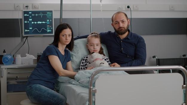 Portret van een droevige familie die in de camera kijkt terwijl ze de handen van de zieke dochter vasthoudt, wachtend op een medische therapiebehandeling tegen de kinderziekte. kind liggend in bed tijdens herstelconsult op ziekenhuisafdeling