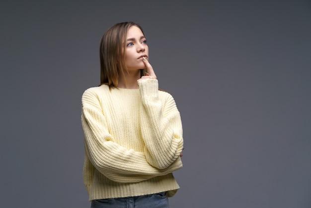 Portret van een droevige jonge vrouw van blanke etniciteit balt haar vuisten in een gele trui op een gra...