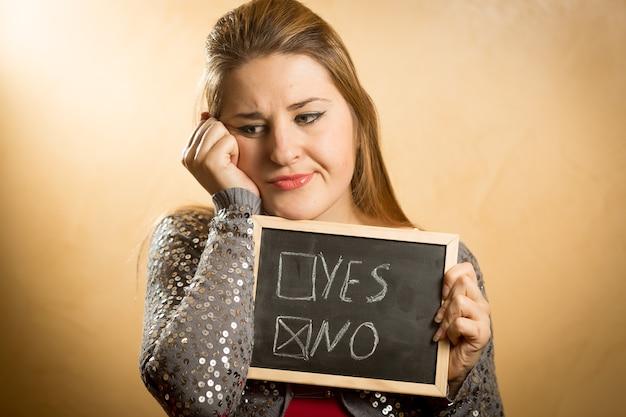 Portret van een droevige vrouw die een bord vasthoudt met een aangevinkt negatief antwoord