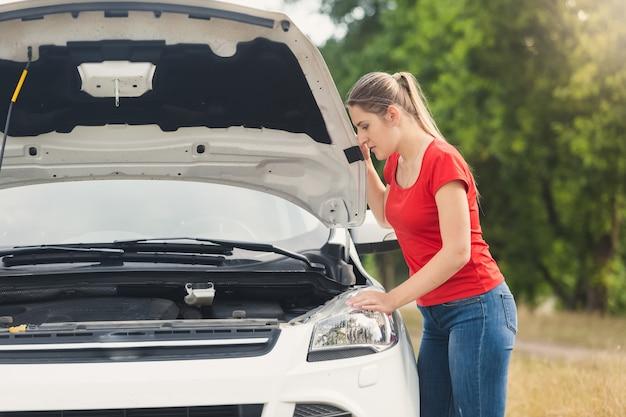 Portret van een droevige vrouw die naar de motor van een kapotte auto kijkt en op hulp wacht