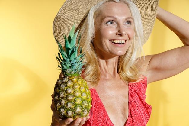 Portret van een dromende blonde vrouw in een rood zwempak en een strohoed die glimlacht terwijl ze vers vasthoudt