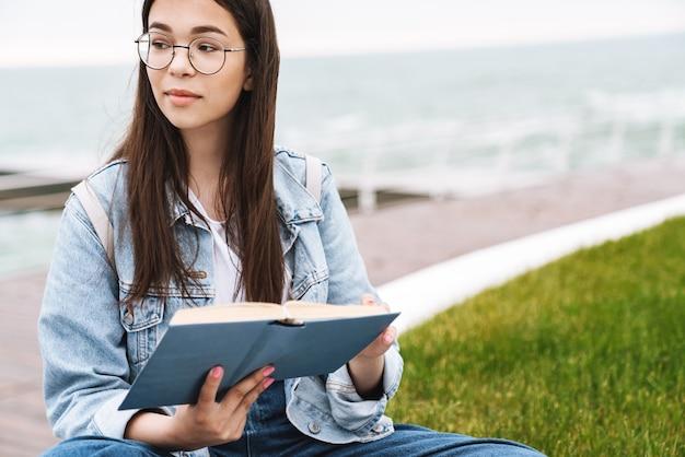 Portret van een dromerig, lief tienermeisje met een bril die een boek leest terwijl ze op groen gras aan de kust zit