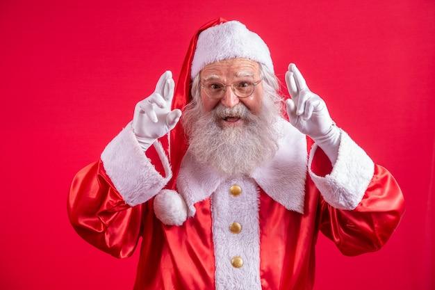 Portret van een dromerige oudere man in het kostuum van de kerstman die vingers kruist en een wens doet, kerstmagie, wintervakantie. indoor studio-opname geïsoleerd op rode achtergrond