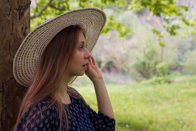 Portret van een dromerige vrouw in een hoed die zich in profiel dichtbij een boom bevindt en vooruit kijkt.