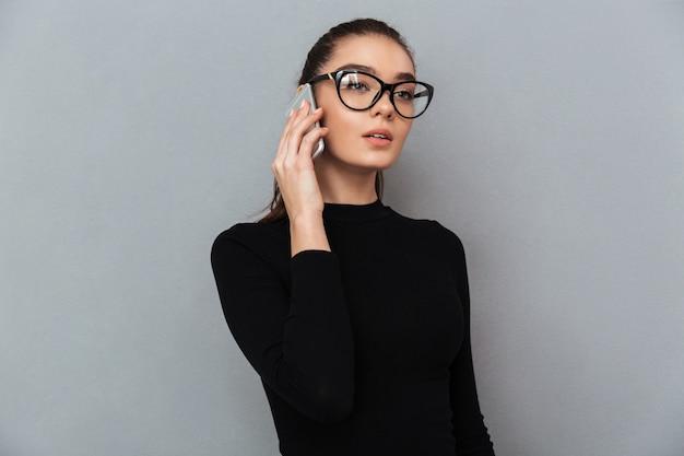 Portret van een drukke jonge vrouw in bril praten