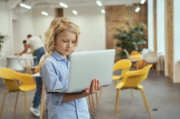 Portret van een drukke kleine jongen die een laptop vasthoudt en gebruikt terwijl hij poseert in een klaslokaal