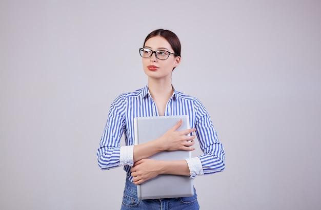 Portret van een drukke vrouw in een gestreept wit-blauw shirt met een bril en een laptop op grijs. werknemer van het jaar, zakelijke dame.