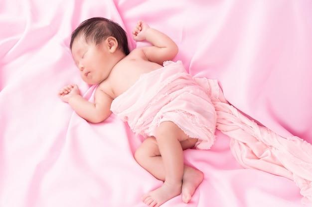 Portret van een één maand oud slapend, pasgeboren babymeisje op een roze deken. concept portret studio mode pasgeboren.