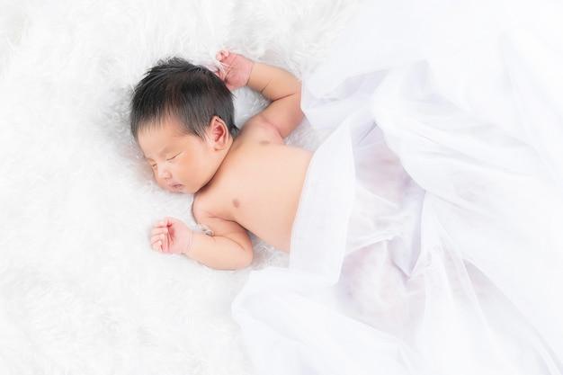 Portret van een één maand oud slapend, pasgeboren babymeisje op een witte deken. concept portret studio mode pasgeboren.