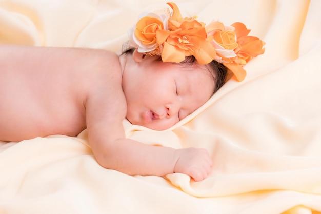 Portret van een één maand oud slapend, pasgeboren babymeisje. ze draagt een bloemenkroon en slaapt op een crème deken. concept portret studio mode pasgeboren.
