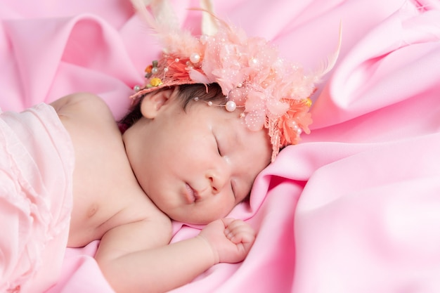 Portret van een één maand oud slapend, pasgeboren babymeisje. ze draagt een bloemenkroon en slaapt op een roze deken. concept portret studio mode pasgeboren.