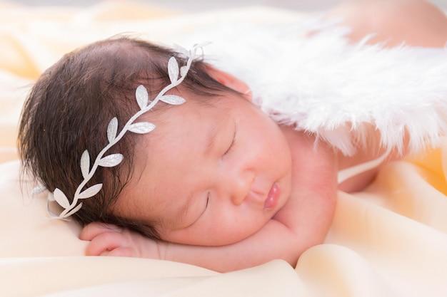 Portret van een één maand oud slapend, pasgeboren babymeisje. ze draagt een witte kroon hoofdband, engelenvleugels en slaapt op een crème deken. concept portret studio mode pasgeboren.