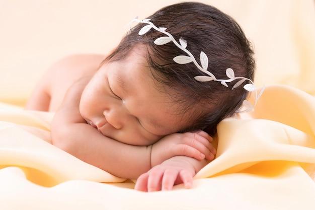 Portret van een één maand oud slapend, pasgeboren babymeisje. ze draagt een witte kroonband en slaapt op een crèmekleurige deken. concept portret studio mode pasgeboren.