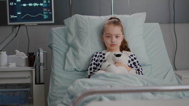 Portret van een eenzaam klein kind dat in de camera kijkt en een teddybeer in handen houdt