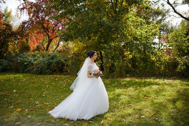 Portret van een eenzame bruid op een achtergrond van een herfst park