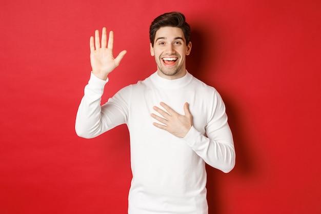 Portret van een eerlijke glimlachende man in een witte trui die een belofte doet en zweert de waarheid te vertellen...
