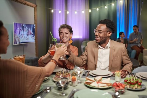 Portret van een elegant koppel van gemengd ras dat geniet van een diner met vrienden binnenshuis en een rammelende bril, kopieer ruimte