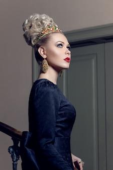 Portret van een elegant model in zwarte jurk, met avondmake-up, naast trap