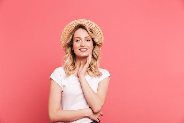 Portret van een elegante blonde vrouw met een strohoed die aan de voorkant glimlacht, geïsoleerd over roze muur