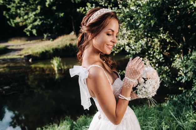 Portret van een elegante bruid in een witte jurk met een boeket in de natuur in een natuurpark m.