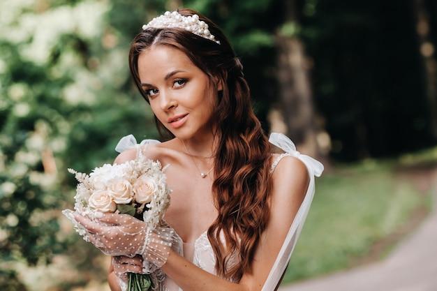 Portret van een elegante bruid in een witte jurk met een boeket in de natuur in een natuurpark.