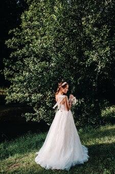 Portret van een elegante bruid in een witte jurk met een boeket in de natuur in een natuurpark