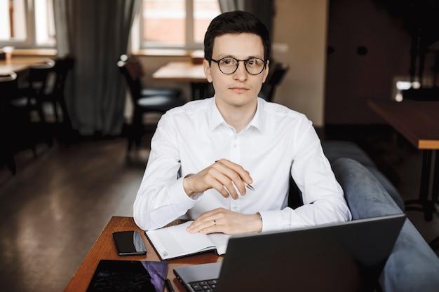 Portret van een elegante manager die op laptop werkt terwijl hij in een café zit, wegkijken met een bril in het wit gekleed.