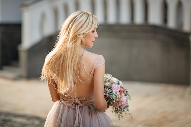 Portret van een elegante mooie vrouw die grijze trouwjurk draagt en op straat poseert. bruid houdt een boeket van pastelkleurige bloemen en groen vast