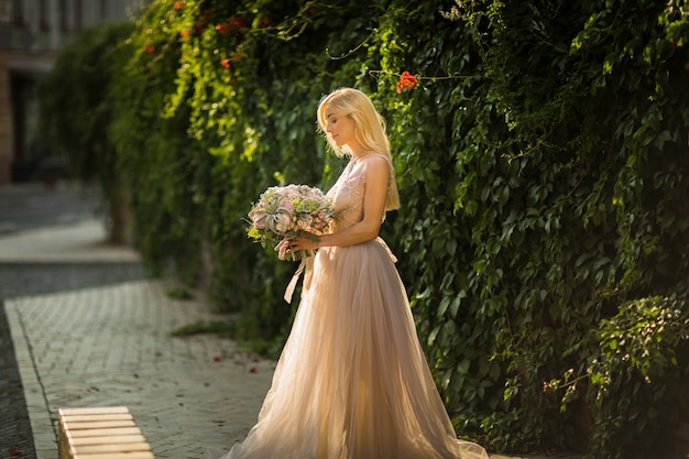Portret van een elegante mooie vrouw grijze trouwjurk dragen en poseren in de straat. bruid houdt een boeket van pastelkleurige bloemen en groen vast
