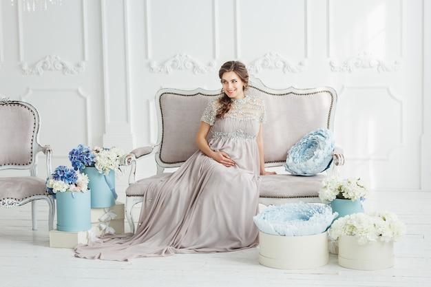 Portret van een elegante mooie zwangere vrouw, gekleed in grijze jurk