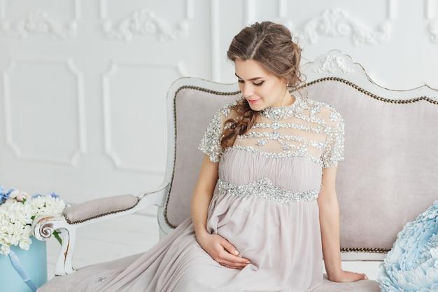 Portret van een elegante mooie zwangere vrouw grijze jurk dragen en zittend op de witte bank met bloemen