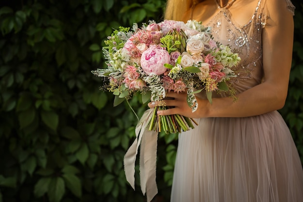 Portret van een elegante, onherkenbare mooie vrouw die een grijze trouwjurk draagt en op straat poseert. bruid houdt een boeket van pastelkleurige bloemen en groen vast