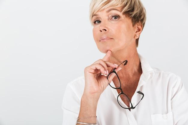 Portret van een elegante vrouw van middelbare leeftijd die een bril vasthoudt en naar een camera kijkt die over een witte muur in de studio wordt geïsoleerd