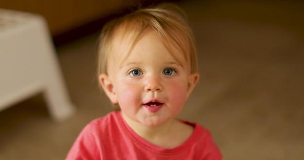 Portret van een elf maanden oud meisje thuis.