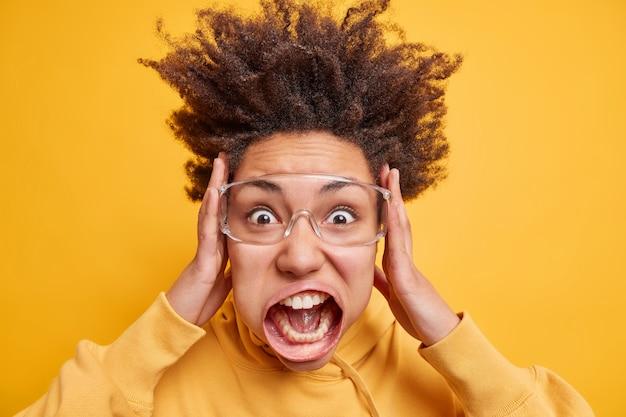 Portret van een emotioneel geschokte vrouw met krullend haar grijpt haar gezicht en schreeuwt luid en houdt de mond wijd open