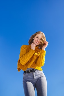 Portret van een emotioneel meisje in een gele trui en kort haar.