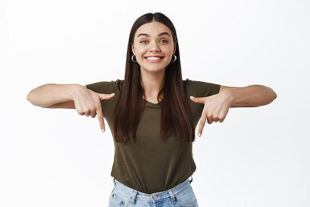 Portret van een enthousiaste glimlachende vrouw die een advertentie op de bodem laat zien, met de vingers naar beneden wijst en gelukkig naar voren kijkt, staande over een witte muur