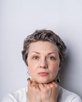Portret van een ernstig ogende vrouw met grijs haar