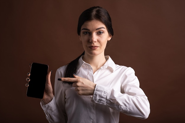 Portret van een ernstige brunette zakenvrouw die met een vinger naar het scherm van haar smartphone in de studio op een bruine achtergrond wijst